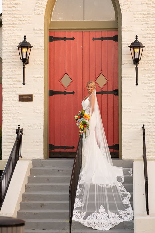 Bride on the front steps of Magnolia Manor and Chapel